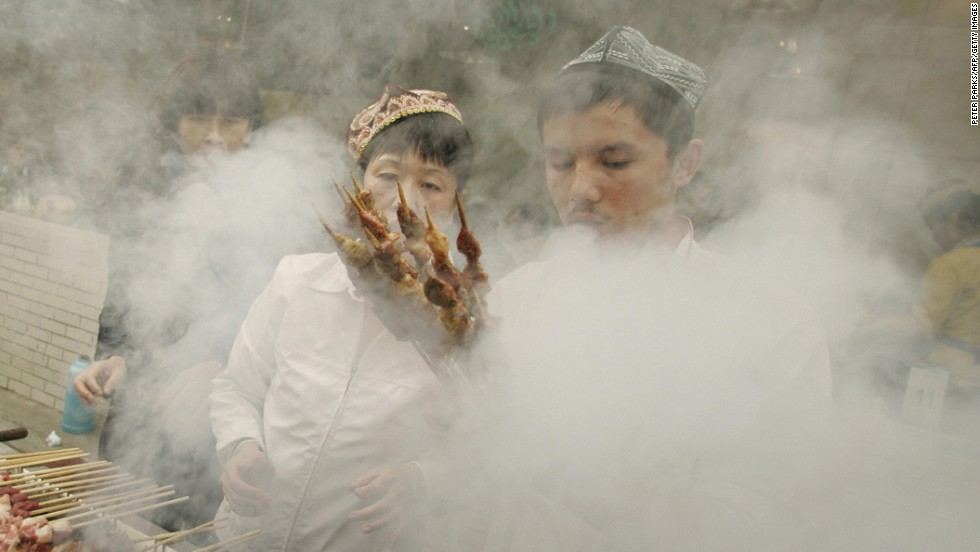 In China ethnic Uyghur Muslims cook lamb outside the Niujie Mosque in Beijing to celebrate Eid al-Fitr. Thousands gather at the capital's oldest and largest mosque for morning prayer and to feast in food stalls and dance in the street.