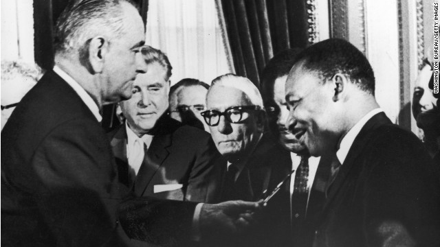 President Lyndon Johnson hands a pen to Rev. Martin Luther King Jr. during the the signing of the Voting  Rights Act in August 1965. (Photo by Washington Bureau/Getty Images)