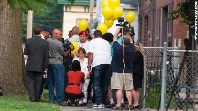 Michelle Knight, center, talks with reporters on Wednesday, August 7,outside the home of Ariel Castro in Cleveland.