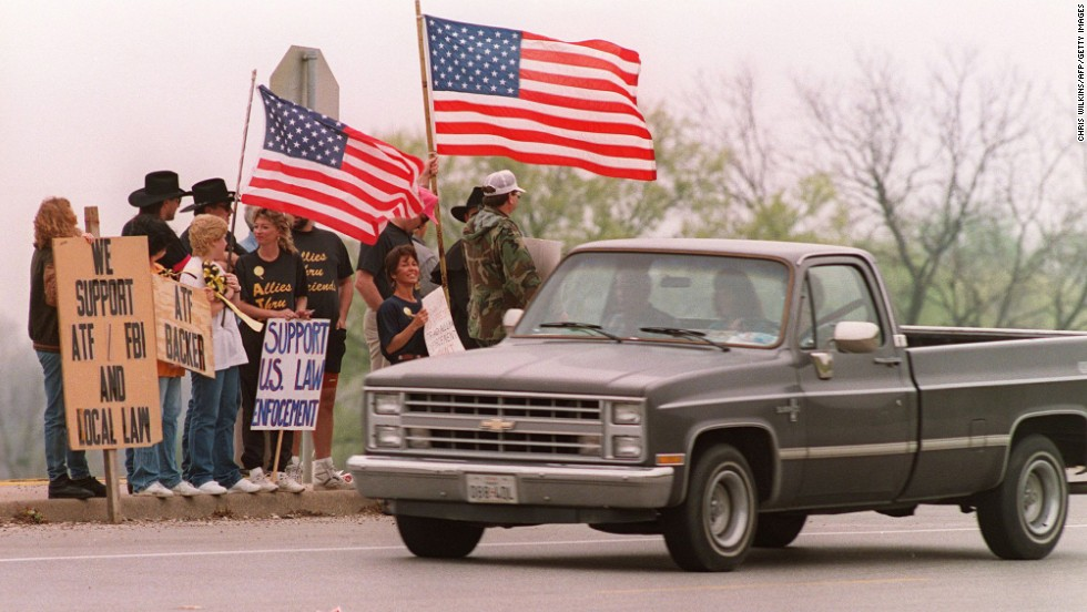Supporters of the ATF stand beside the turnoff to the Branch Davidian compound on March 28, 1993.