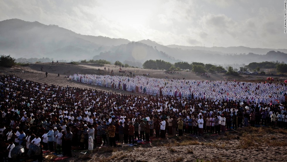 "AUGUST 8 - YOGYAKARTA, INDONESIA : Indonesian Muslims perform <a href=""http://cnn.com/2013/08/08/world/sweet-eid-break-fast-treats/index.html?hpt=hp_c5"">Eid Al-Fitr</a> prayers on Parangkusumo beach on August 8. Eid Al-Fitr marks the end of Ramadan, the Islamic month of fasting, and begins after the sighting of a new crescent moon."
