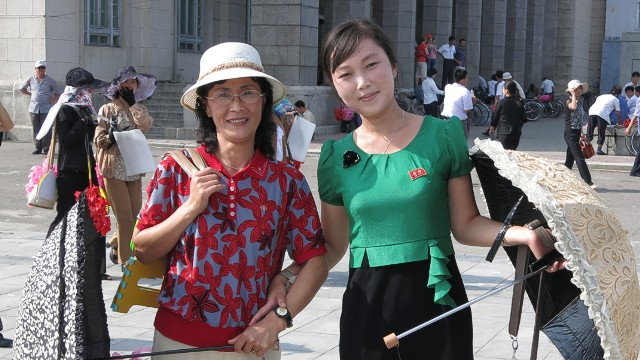 "Two North Koreans display their ""Kim pins."""