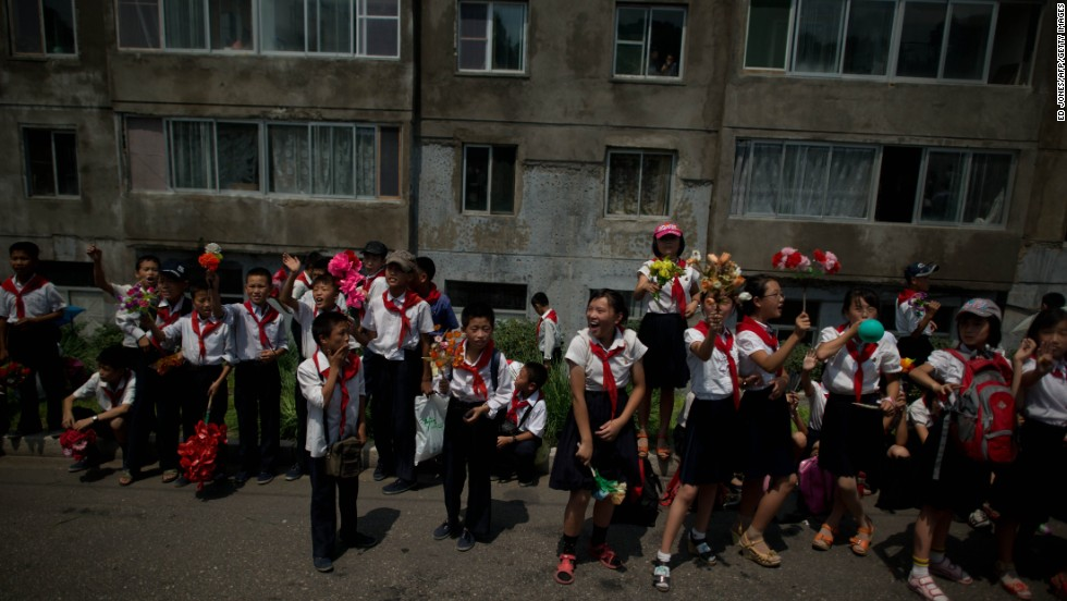 North Korean children wait on a roadside following a parade marking the 60th anniversary of the Korean war armistice in Pyongyang.
