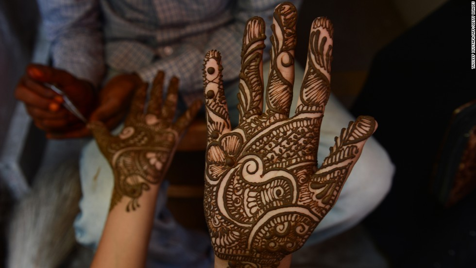 "A young Kashmiri woman admires her hand after it was decorated with henna at a market ahead of the festivities on August 8. The <a href=""http://religion.blogs.cnn.com/2013/07/12/the-belief-blog-guide-to-ramadan/"">word Ramadan derives</a> from the Arabic ramida or ar-ramad, meaning a fierce, burning heat."