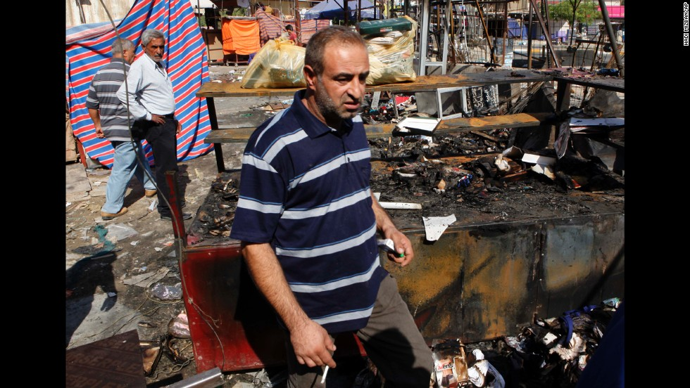 People inspect the scene of a bombing at a store in Baghdad on August 11.