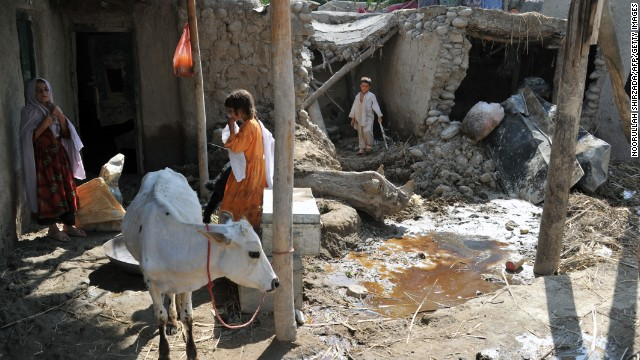 Residents stand in the compound of their flood-damaged home in Surobi district of Kabul province on August 7.