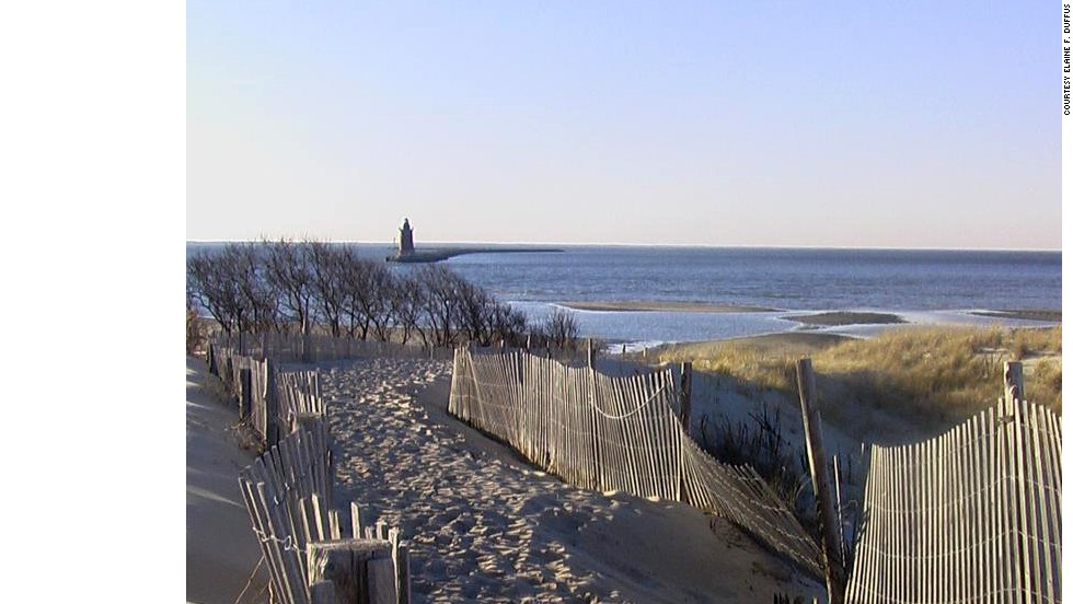 The Delaware Breakwater East End Light stands guard in the distance beyond the trails and dunes of the beach near Lewes, Delaware.