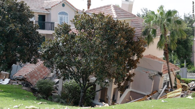 A portion of a building is in a sinkhole Monday, Aug. 12, 2013 in Clermont, Fla.   The sinkhole, 40 to 50 feet in diameter, opened up overnight and damaged three buildings at the Summer Bay Resort.  (AP Photo/John Raoux)