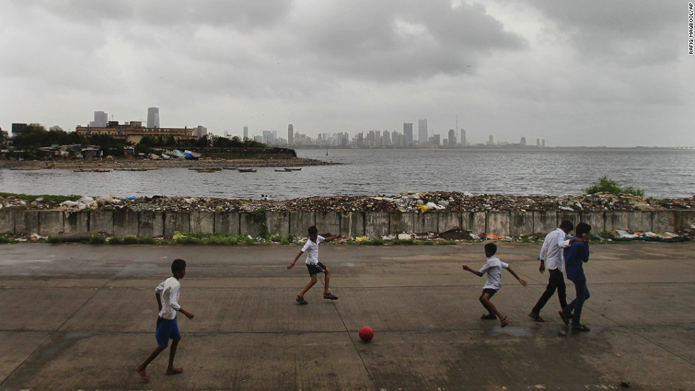 Indian children play soccer on the Arabian Sea coast as monsoon clouds hang low over Mumbai on Tuesday, August 13.