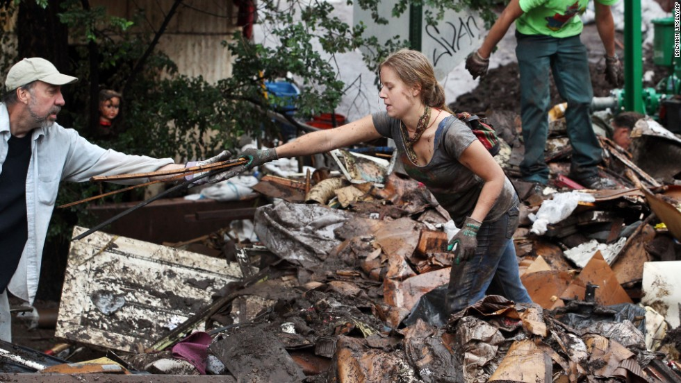 "Erin Dettweiler, center, works with other local volunteers to clear away tons of mud-caked debris on August 13 after a recent <a href=""http://www.cnn.com/2013/08/10/us/weather/index.html"">flash flood in Manitou Springs, Colorado</a>."