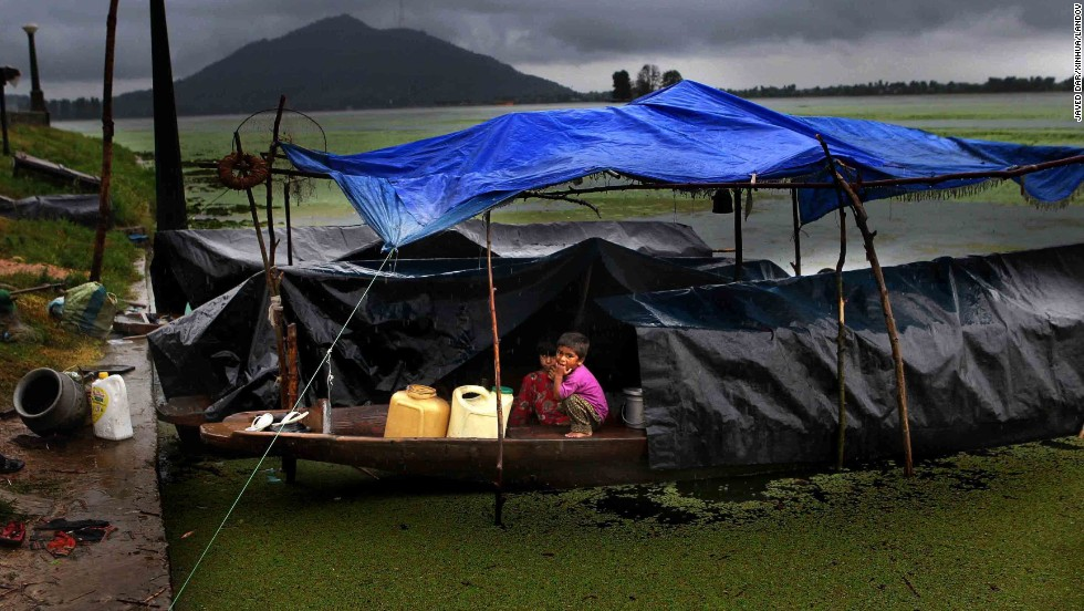 Children look out at the rain from under a makeshift shelter on August 13 in Srinagar, the summer capital of Kashmir.