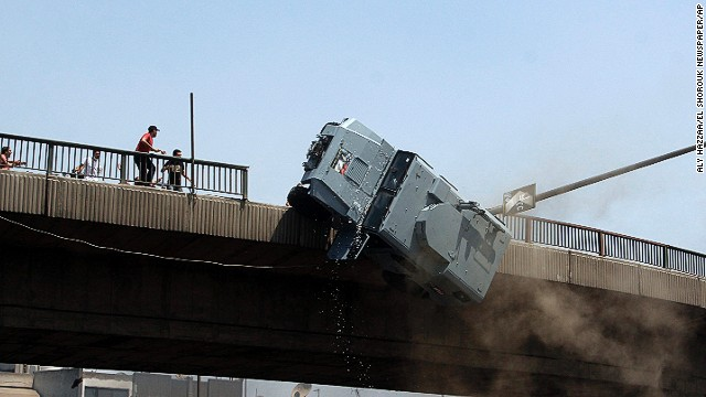 A police vehicle is pushed off of the 6th of October bridge by supporters of ousted Egyptian President Mohamed Morsy in Cairo on Wednesday, August 14.