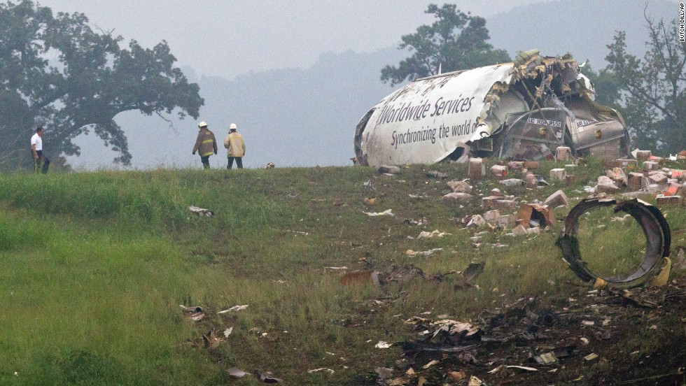 Fire crews investigate where a UPS cargo plane lies on a hill about a half-mile from the runway.