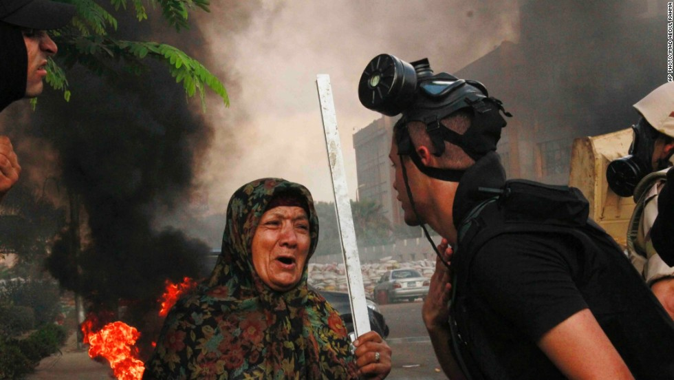 "AUGUST 14 - CAIRO, EGYPT: A woman speaks to a member of the Egyptian security forces who are clearing a sit-in by supporters of ousted President Mohamed Morsy, near the Cairo University campus in Giza on August 14. <a href=""http://cnn.com/2013/08/14/world/meast/egypt-protests/index.html?hpt=imi_c1"">Security forces stormed two makeshift camps</a>, bulldozing tents and escorting away hundreds of protesters."