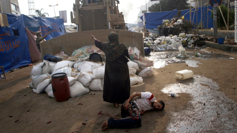 A woman tries to stop a military bulldozer from hurting a wounded youth during clashes on August 14, 2013, in eastern Cairo.