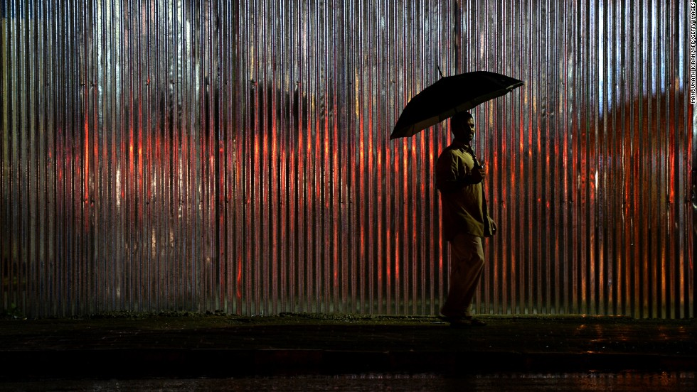 A pedestrian walks with an umbrella as rain falls in Bangalore, India, on Wednesday, August 14.