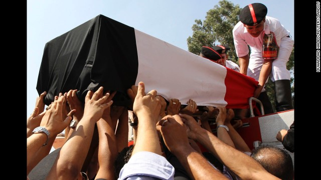 People reach for a coffin on Thursday, August 15, during a funeral for policemen killed during clashes yesterday in Cairo, Egypt.