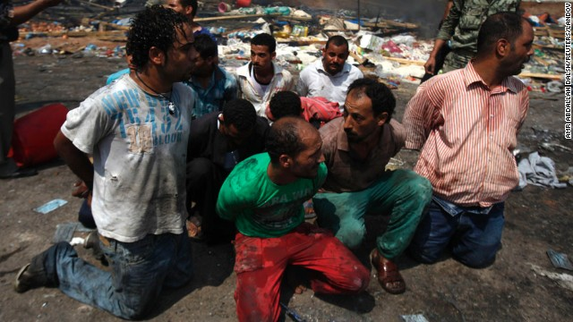 Men are detained near a burnt section of Rabaa Al-Adawiya mosque in Cairo on August 15.