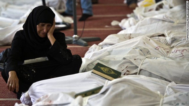 An Egyptian woman mourns over the body of her daughter wrapped in shrouds at a mosque in Cairo on August 15, 2013, following a crackdown on the protest camps of supporters of ousted Islamist president Mohamed Morsi the previous day. The day's violence was Egypt's worst in decades, exceeding even that seen during the 18-day uprising that ousted president Hosni Mubarak. AFP PHOTO / KHALED DESOUKI (Photo credit should read KHALED DESOUKI/AFP/Getty Images)