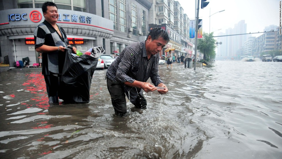 Two men clear a blocked catch basin on a street in Shenyang, the capital of northeast China's Liaoning Province, on August 16.