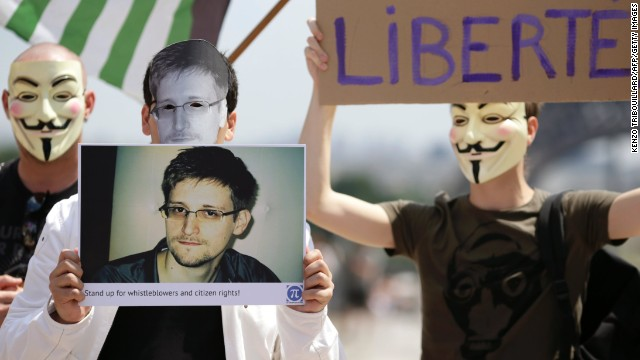A demonstrator holds up a picture of the former technical contractor of the US Central Intelligence Agency Edward Snowden during a demonstration in support of Snowden at the Place du Trocadero in front of the Eiffel tower in Paris on July 7, 2013. Around forty people, mostly activists from organizations defending rights and freedom on the internet, gathered in support of Snowden, who leaked information on data spying programs of the USA and Great Britain in June 2013 and has sought asylum in 21 countries, according to WikiLeaks. AFP PHOTO / KENZO TRIBOUILLARD        (Photo credit should read KENZO TRIBOUILLARD/AFP/Getty Images)