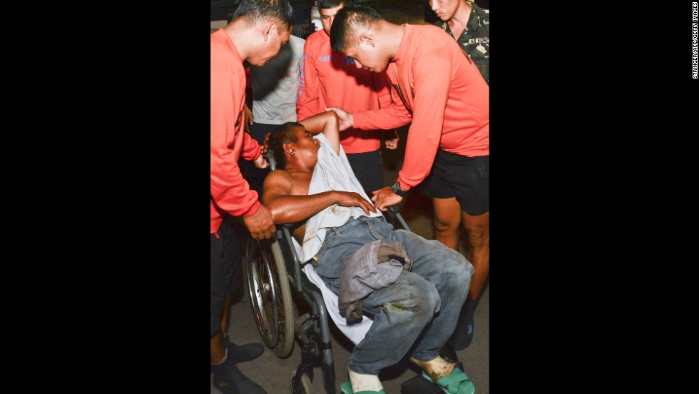 A survivor in a wheelchair is assisted as he arrives at the hospital on August 17.
