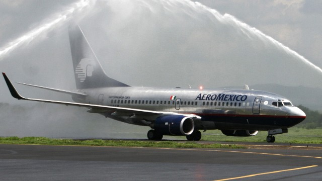 Managua, NICARAGUA: An Aeromexico plane crosses below an arc of water made by firefighters to mark the Mexico-Managua non stop inaugural flight 04 June 2007 in Managua.AFP PHOTO/Miguel ALVAREZ (Photo credit should read MIGUEL ALVAREZ/AFP/Getty Images)