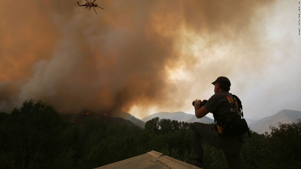 John Koth climbs to the roof of a neighbor's house near Hailey to photograph the blaze on August 16.
