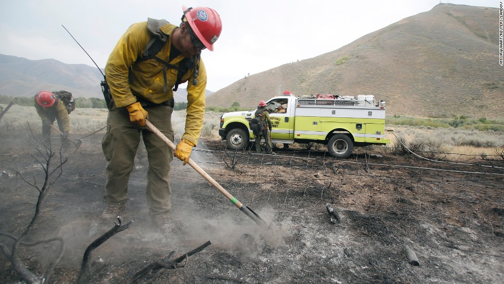 Firefighters clear an area burned by the Beaver Creek Fire on August 17. Approximately 1,200 firefighters are working the blaze, with the help of helicopters, bulldozers and conventional engines.