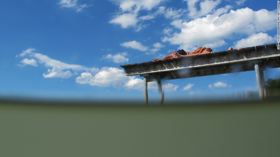 A man and a woman take in some rays on a bridge at a lake near Fussen in Germany's Bavaria state on August 16.