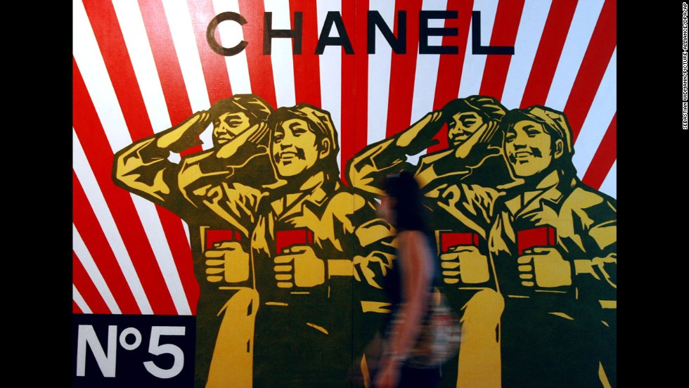 A woman walks past a Chanel-inspired piece by political pop artist Wang Guangyi in the Hamburger Kunsthalle art gallery in Hamburg, Germany.