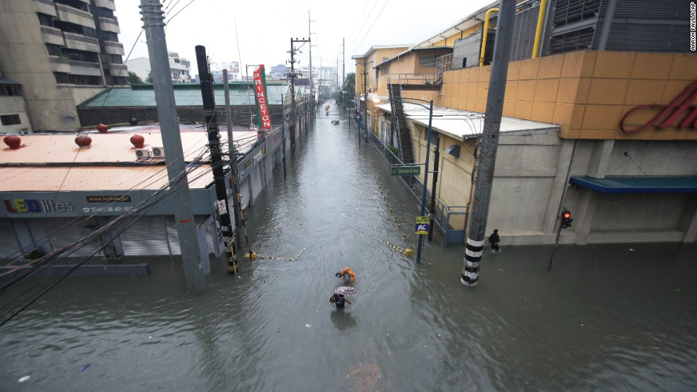 People wade through a flooded street in Makati on August 20.