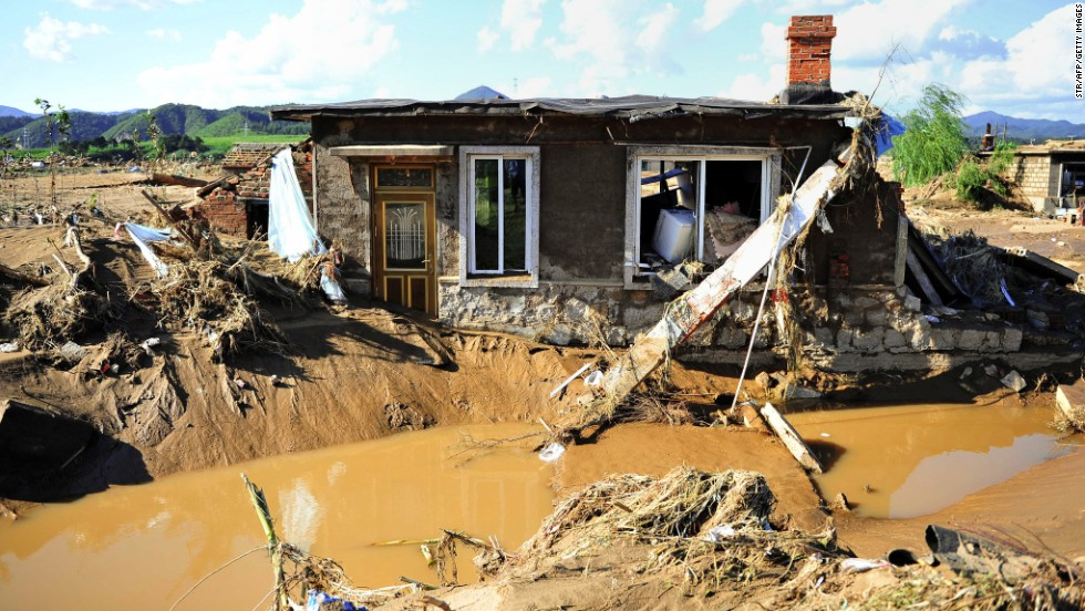 A damaged house sits in mud and floodwater in China's Liaoning province on August 19.