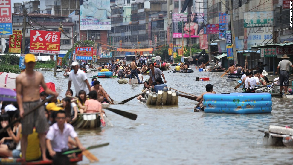 People travel on boats and makeshift rafts down a flooded street in Shantou, China, on August 19.