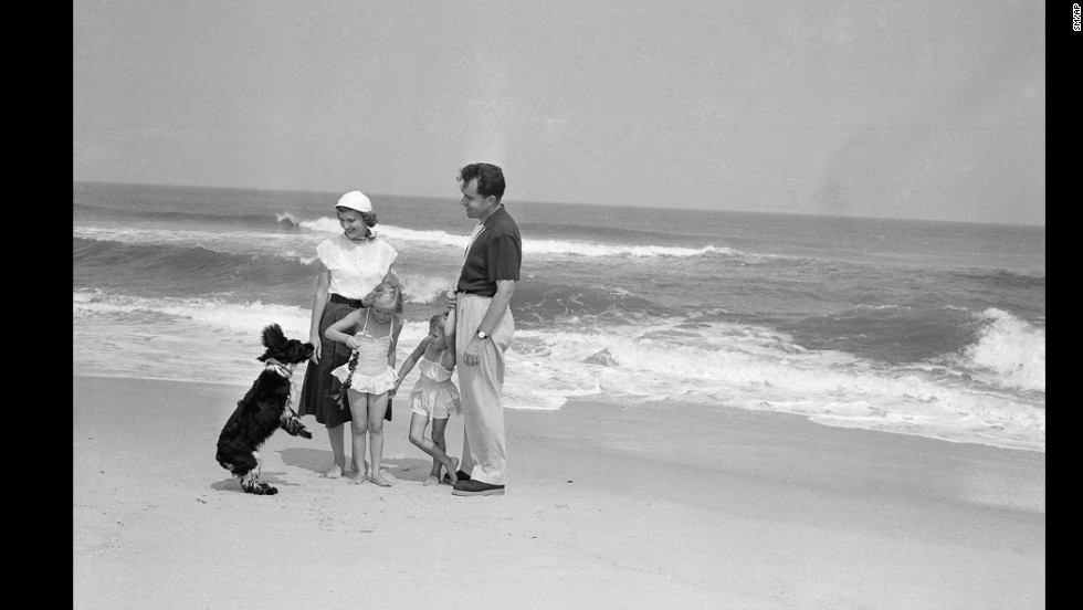 President Richard Nixon, his wife and two daughters play with their pet cocker spaniel Checkers on the beach at Mantoloking, New Jersey, in 1953.