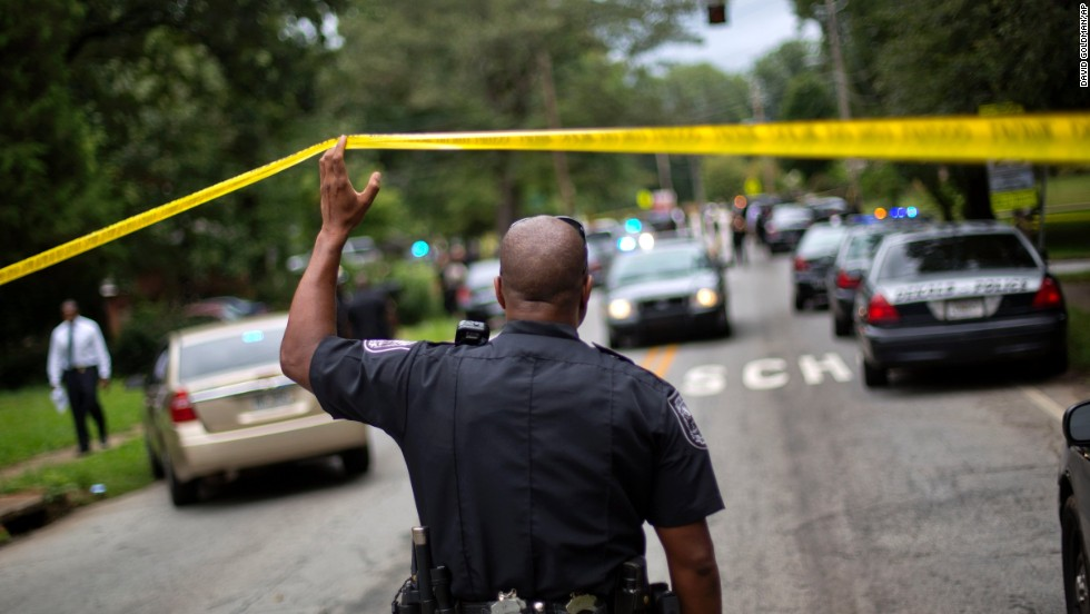 A police officer stands at the scene after the shooting. The school is located about seven miles east of downtown Atlanta.