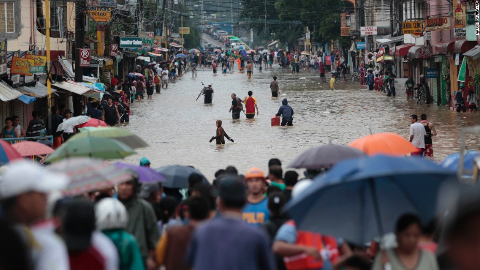 People cross a flooded street to evacuate to higher ground in Marikina City on Tuesday, August 20.