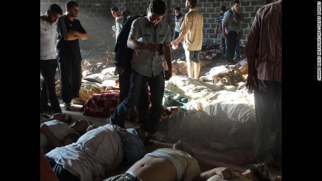 People inspect bodies of children and adults laying on the ground after they were killed, Syrian rebels claim, in a chemical attack by pro-government forces in eastern Ghouta, on the outskirts of Damascus on August 21, in this photo released by the Syrian opposition's Shaam News Network.