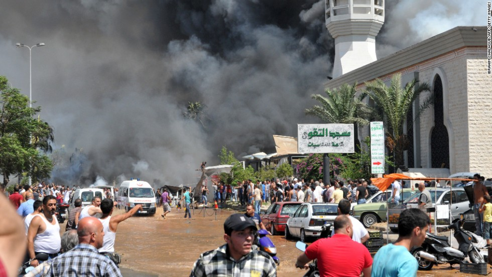 Smoke is seen above people gathering outside a mosque on the site of a powerful explosion in the northern Lebanese city of Tripoli on Friday, August 23. Two bombings killed dozens of people. The first blast occurred near a mosque led by a Sunni sheikh known for his links to Syrian rebels, Lebanon's state-run National News Agency said. The second occurred minutes later near another mosque, close to the residence of acting Prime Minister Najib Mikati.