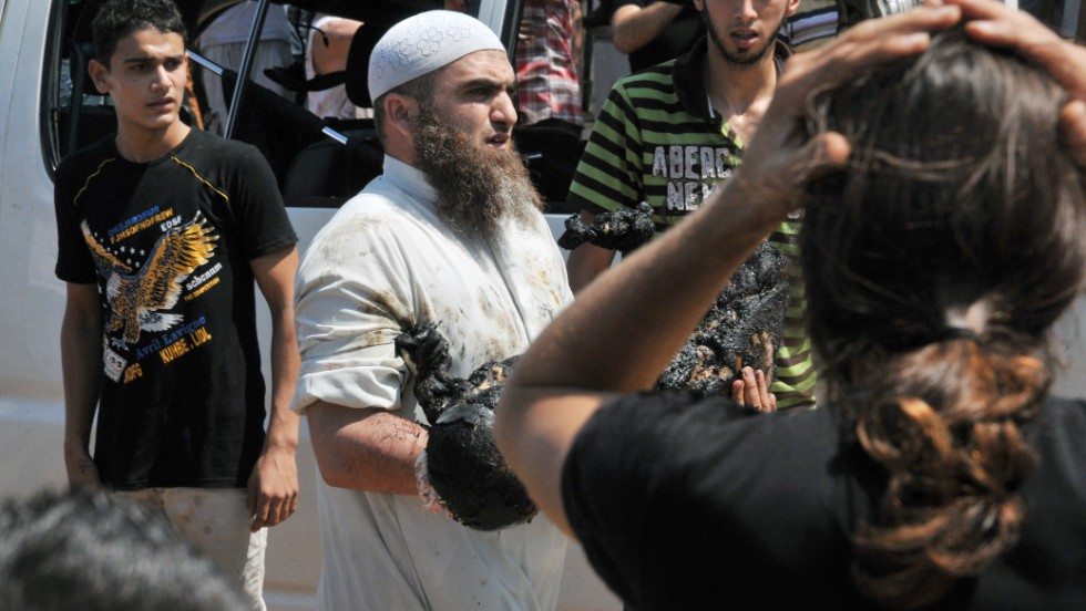 A man carries the burnt body of a victim of one of the explosions outside the al Taqwa mosque.