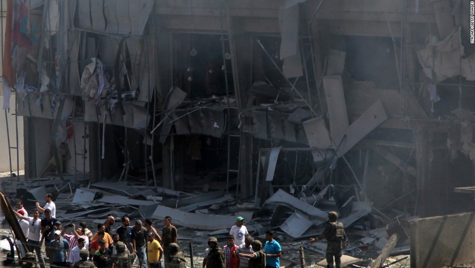 People stand in front of a severely damaged building as they gather outside the al Salam mosque.