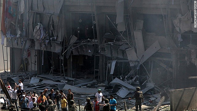Lebanese citizens stand in front of a severely damaged building as they gather outside al-Salam mosque, near the house of former Lebanese police chief Ashraf Rifi, at the site of a powerful explosion in the northern Lebanese city of Tripoli on August 23, 2013.