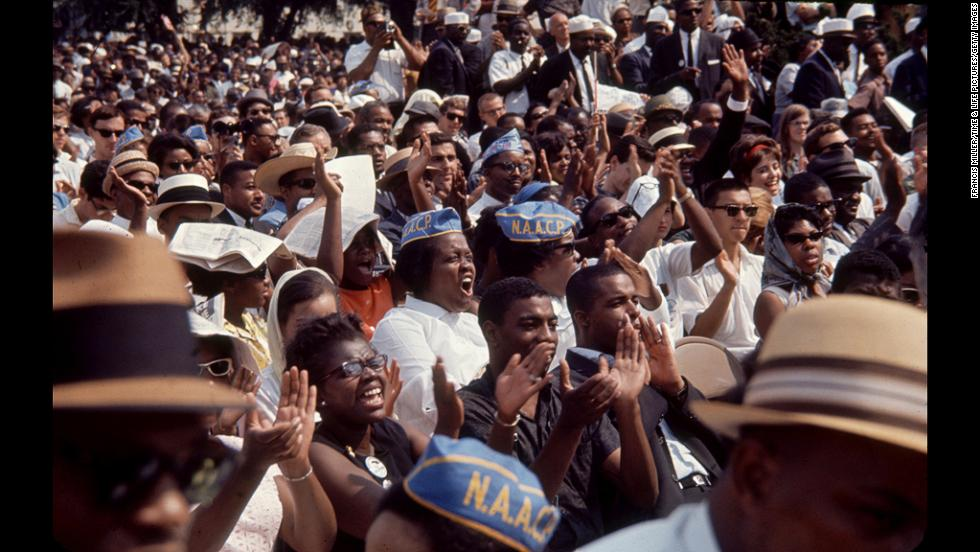 Civil rights protesters clap and cheer. An estimated 250,000 people participated in the march.