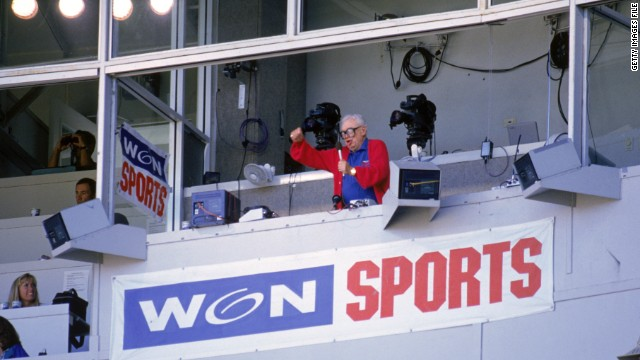 "Chicago Cubs baseball announcer Harry Caray conducts fans singing ""Take Me Out to the Ball Game"" from his television booth in 1996"