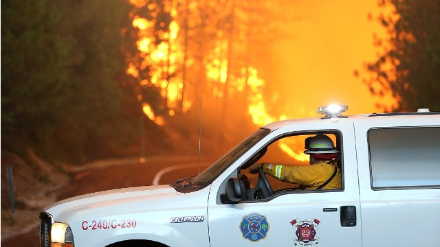 A firefighter stops his vehicle as a massive wall of fire from the Rim Fire consumes trees along highway 120 on August 24, 2013 near Groveland, California.