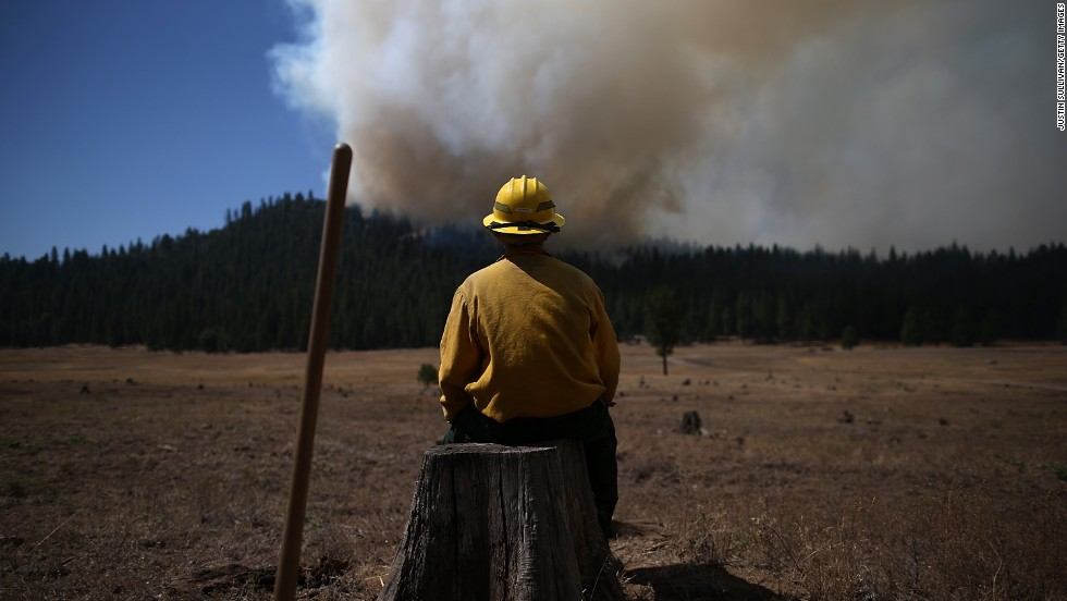 U.S. Fish and Wildlife Service firefighter Corey Adams sits on a tree stump as he monitors the Rim Fire near Groveland on August 25.