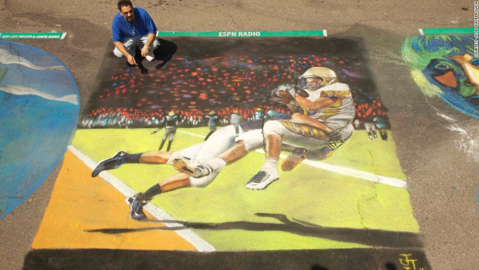 Artist Julio Jimenez crouches next to his image of a touchdown-saving tackle in San Luis Obispo, California.