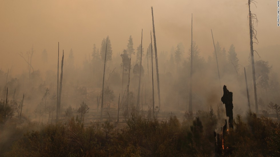 "AUGUST 26 - CALIFORNIA, UNITED STATES: Smoke rises from smoldering trees as <a href=""http://cnn.com/2013/08/26/us/california-yosemite-wildfire/index.html?hpt=hp_t3"">more than 3,400 firefighters battle the Rim Fire near Yosemite National Park</a> on Sunday, August 25. The wildfire has become the <a href=""https://twitter.com/CALFIRE_PIO/statuses/371822607345016833"" target=""_blank"">14th largest in state history</a>, devouring nearly 144,000 acres and an area about the size of the city of Chicago."