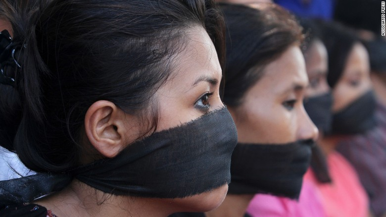 Women cover their mouths in a 2013 protest against rape in Guwahati, India.