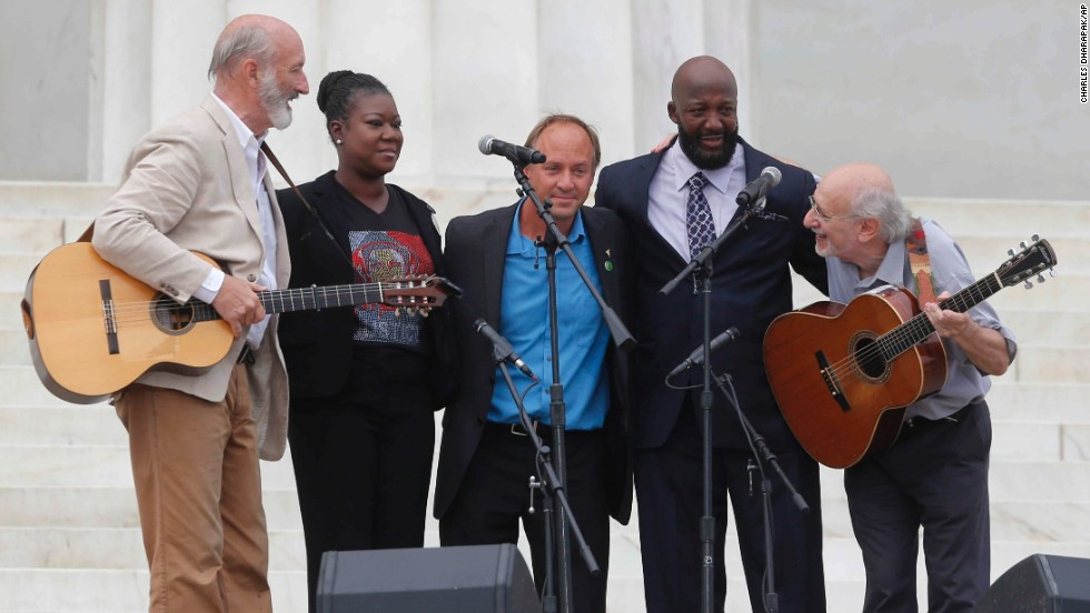 Peter Yarrow, left, and Paul Stookey, right, of the folk trio Peter, Paul and Mary, stand with Trayvon Martin's parents, Sybrina Fulton and Tracy Martin, at Wednesday's celebration.